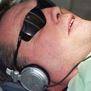 Man i solglasögon lyssnar på musik i hörlurar hos tandläkaren.