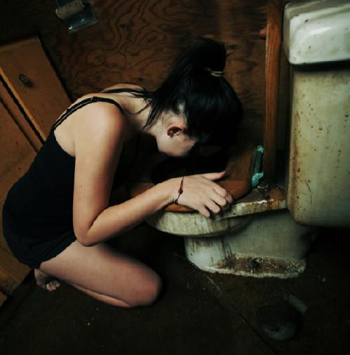 Flicka med ätstörningar kräks i en smutsig toalett
