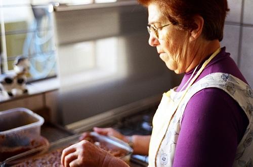Äldre kvinna i kök lagar mat.