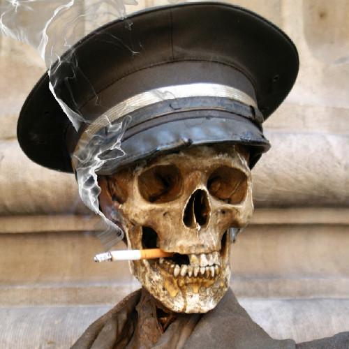 Dödskalle med flera saknade tänder röker en cigarett