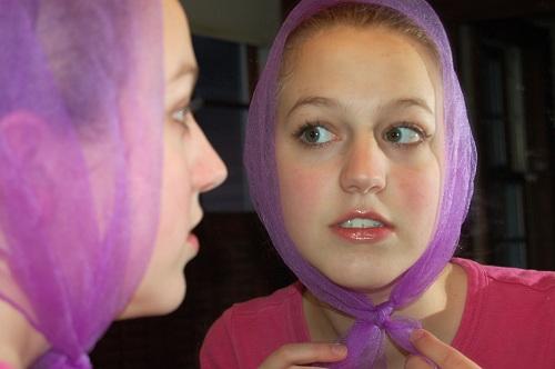 Flicka speglar sig och betraktar sin tänder